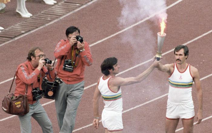 Олимпийский чемпион Сергей Белов (справа) принимает факел с олимпийским огнем из рук трехкратного олимпийского чемпиона Виктора Санеева (слева).