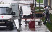 Медики перевозят тело умершего на территории карантинного центра в Коммунарке.