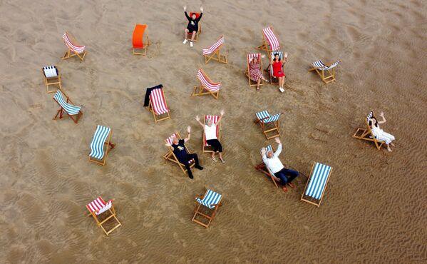 Люди позируют для фотографии, сидя в шезлонгах на пляже в Блэкпуле, Великобритания - Sputnik Южная Осетия