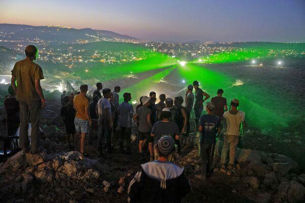 Израильские поселенцы на аванпосте Эвиатар смотрят, как палестинские протестующие направляют на них лазерные лучи из близлежащей деревни Бейта - Sputnik Южная Осетия