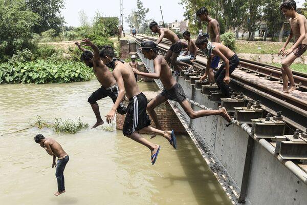 Подростки прыгают в канал, чтобы освежиться в жаркий летний день на окраине Амритсара, Индия - Sputnik Южная Осетия