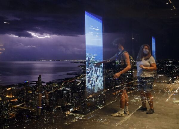 Люди отражаются на стеклянной стене Уиллис-Тауэр в Чикаго на фоне молний над озером Мичиган - Sputnik Южная Осетия