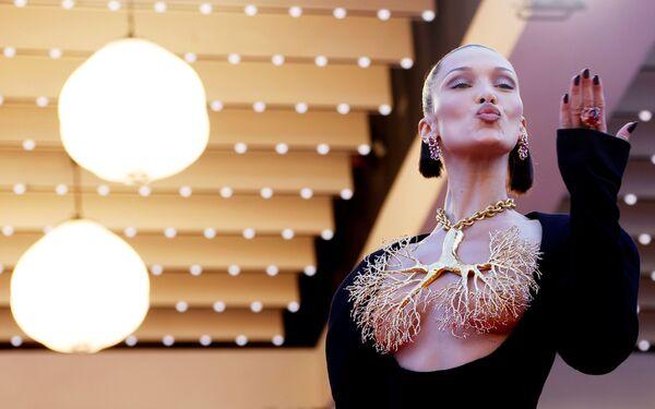 Роскошный наряд Беллы Хадид произвел фурор. Черное облегающее платье-футляр с экстремально глубоким декольте, дополненное массивным золотым украшением в виде бронхов, называют одним из лучших в истории фестиваля. Выглядит впечатляюще, особенно в период пандемии. - Sputnik Южная Осетия