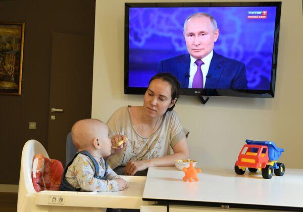 Женщина с ребенком смотрят трансляцию прямой линии с президентом РФ Владимиром Путиным. - Sputnik Южная Осетия