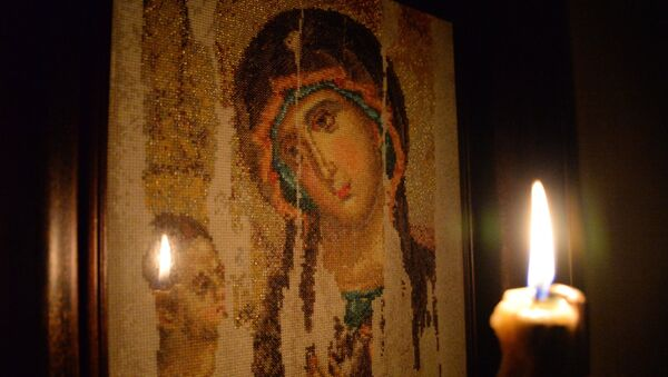 Горящая свеча на фоне вышитого изображения Казанской иконы Божьей матери - Sputnik Южная Осетия