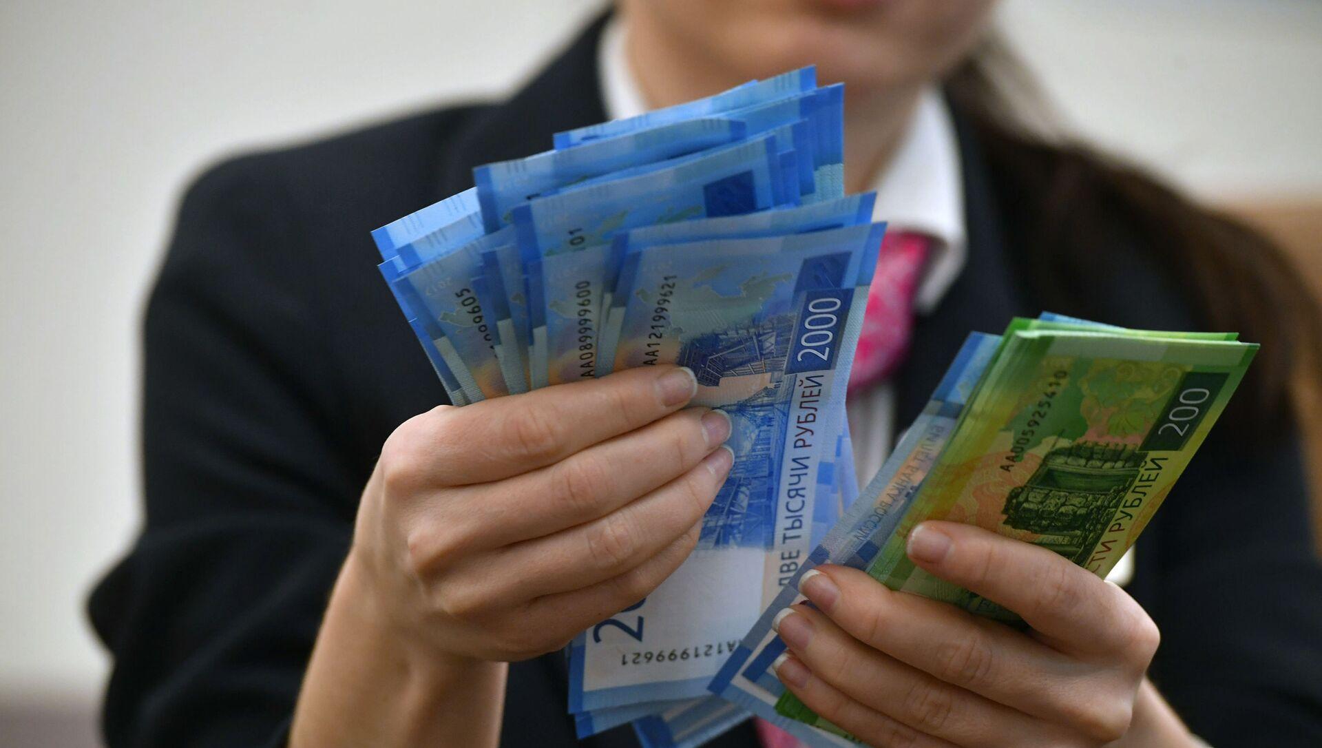 Сотрудница банка пересчитывает денежные купюры - Sputnik Южная Осетия, 1920, 10.10.2021